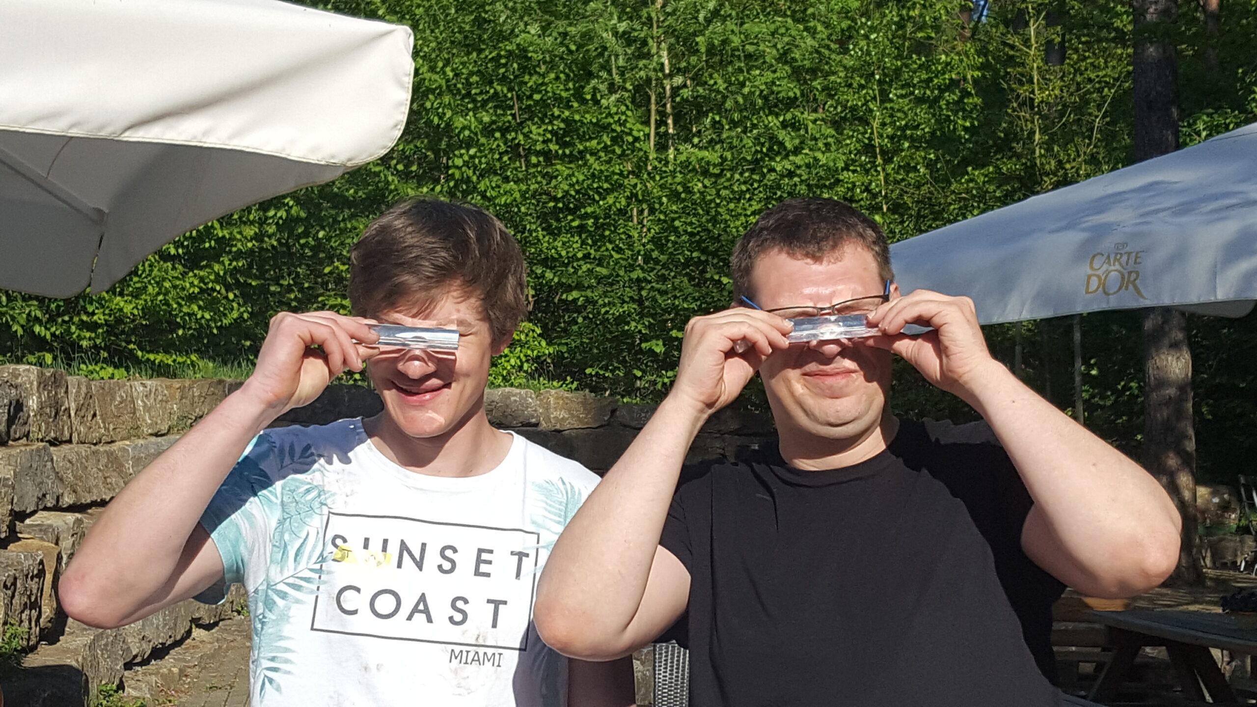 Zwei Teilnehmer des Projektes Aplaus halten sich Metallteile vor die Augen